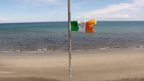 Irlandzkiej flagi państowowej Tricolour latanie morzem w Carnlough Północnym - Ireland