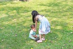 A irmã asiática ciao seu irmão mais novo no jardim exterior imagens de stock royalty free