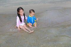Irmã asiática e seu irmão mais novo no terno de natação que joga ondas do mar na praia fotografia de stock