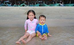 Irmã asiática pequena de sorriso e seu irmão mais novo no terno de natação que joga ondas do mar na praia imagem de stock royalty free