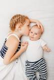 Irmã caucasiano da menina que guarda o beijo do bebê pequeno, encontrando-se na cama fotografia de stock