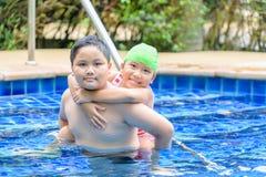 Irmã da terra arrendada do irmão no seu para trás na piscina imagens de stock