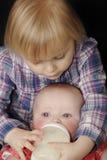 Irmã de alimentação do bebê da rapariga imagem de stock royalty free