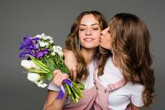 irmã de beijo gêmea nova atrativa com ramalhete imagens de stock