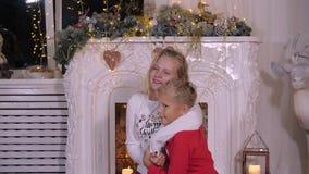 Irmã de sorriso que abraça o irmão mais novo no fundo da chaminé do Natal video estoque