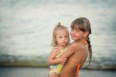 A irmã do espantalho abraça lovingly sua irmã com Síndrome de Down imagem de stock royalty free