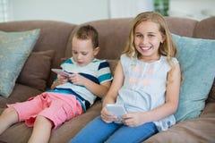 Irmã e irmão de sorriso que sentam-se no sofá usando o telefone celular na sala de visitas Imagens de Stock
