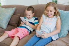 Irmã e irmão de sorriso que sentam-se no sofá usando o telefone celular na sala de visitas Fotos de Stock Royalty Free