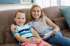 Irmã e irmão de sorriso que sentam-se no sofá usando o telefone celular na sala de visitas em casa Fotografia de Stock Royalty Free