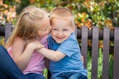 Irmã e irmão novos Snuggle On um banco no parque foto de stock royalty free