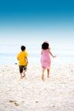 Irmã e irmão que funcionam na praia arenosa foto de stock