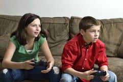 Irmã e irmão que jogam um jogo video Foto de Stock Royalty Free