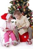 Irmã e irmão que mostram presentes de Natal Fotografia de Stock