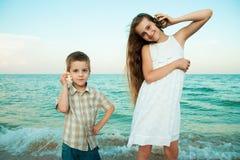 A irmã e o irmão na noite encalham com os shell fotografia de stock royalty free
