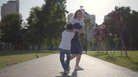 Irmã mais idosa alegre que gerencie ao redor com o irmão mais novo que guarda as mãos no parque do verão Lazer fora amig?vel video estoque
