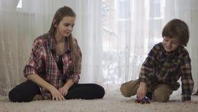 Irmã mais idosa e irmão mais novo que jogam junto o assento no assoalho no tapete macio O menino que joga com filme