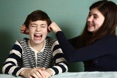 A irmã puxa suas orelhas do menino do irmão devido à aposta fotos de stock