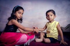 irmã que amarra a linha do rakhi no pulso do irmão Imagens de Stock