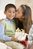 Irmã que dá a seu irmão um beijo Fotos de Stock