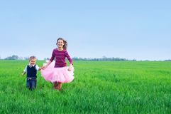 Irmã que runing com seu brather na grama Foto de Stock Royalty Free