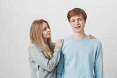 Irmã que tenta consolar o irmão que perdeu na competição Retrato de importar-se a mulher bonito loura preocupada que abraça e imagens de stock