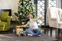 A irmã que testa vidros da realidade virtual aproxima a árvore do ano novo imagens de stock