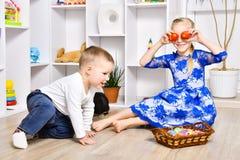 Irmão alegre e irmã que jogam na Páscoa imagens de stock royalty free