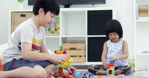 Irmão asiático e irmã que jogam o bloco plástico junto em casa com cara do sorriso video estoque