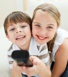 Irmão bonito e irmã que prestam atenção à tevê Imagem de Stock