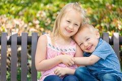 Irmão da criança e irmã Embrace On um banco no parque foto de stock royalty free