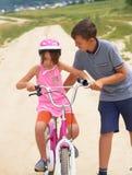 Irmão da juventude que ensina sua irmã mais nova montar uma bicicleta Menina em um capacete protetor cor-de-rosa em passeios cor- imagens de stock