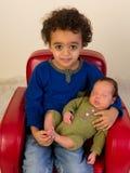 Irmão de sorriso com irmão recém-nascido fotografia de stock royalty free