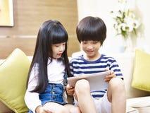 Irmão e irmã asiáticos que usa a tabuleta digital fotografia de stock royalty free