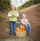 Irmão e irmã Children nas etapas de madeira com abóboras que canta Fotos de Stock