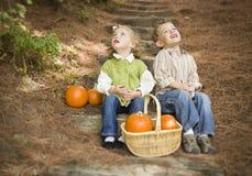 Irmão e irmã Children nas etapas de madeira com abóboras que canta Fotos de Stock Royalty Free
