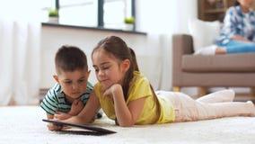 Irmão e irmã com tablet pc em casa video estoque
