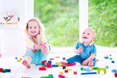 Irmão e irmã de Laughings que jogam com bloco colorido Fotografia de Stock