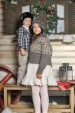 Irmão e irmã em um banco na frente da casa no inverno Foto de Stock Royalty Free
