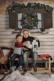 Irmão e irmã em um banco na frente da casa no inverno Fotos de Stock Royalty Free