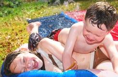 Irmão e irmã em Waterplay fotografia de stock