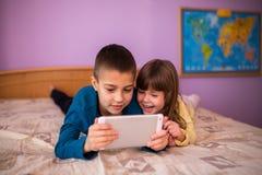 Irmão e irmã Having Fun com tabuleta em casa Fotos de Stock Royalty Free