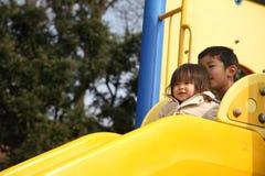 Irmão e irmã japoneses na corrediça Imagens de Stock