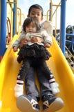 Irmão e irmã japoneses na corrediça Foto de Stock Royalty Free