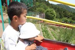 Irmão e irmã japoneses na corrediça Fotos de Stock