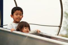 Irmão e irmã japoneses na corrediça Fotos de Stock Royalty Free