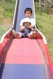 Irmão e irmã japoneses na corrediça Imagens de Stock Royalty Free