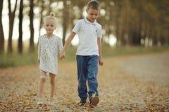 Irmão e irmã na estrada secundária Fotografia de Stock