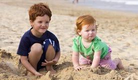 Irmão e irmã na praia Fotografia de Stock Royalty Free