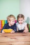 Irmão e irmã pequenos que usa smartphones junto Foto de Stock