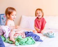 Irm?o e irm? perniciosos Play em uma pilha da lavanderia na cama Conceito de fam?lia imagem de stock royalty free